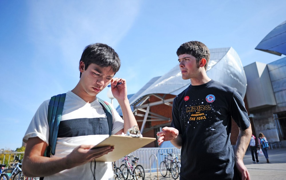 MPIRG youth vote organizer Andy Pearson, right, assists computer science freshman Alex David in completing his voter registration Tuesday afternoon on the Washington Avenue Bridge. Similar events were held by Grace University Lutheran Church and League of Women Voters Minneapolis as part of National Voter Registration Day.