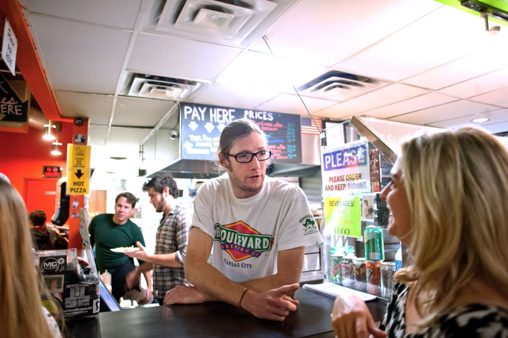 Mesa Pizza general manager Matt Tomkins serves crowds of late-night customers Saturday night in Dinkytown. Tomkins says he likes the challenge of working late nights.