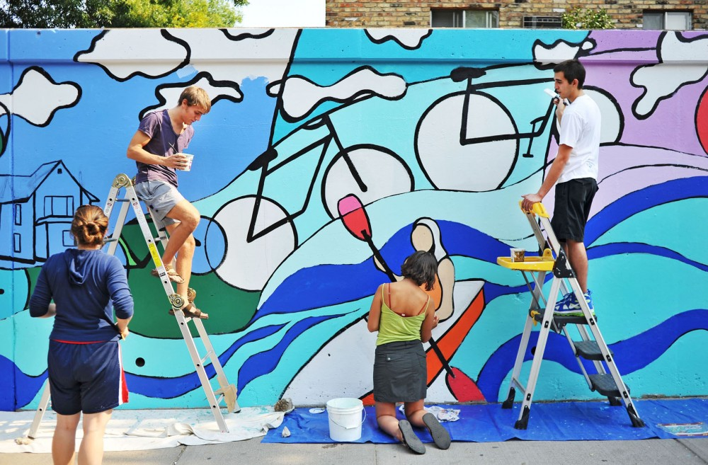 Artist Carly Schmitt , left, supervises volunteers Tim Johnson, Megan McCrunb and Alex Kern as they work on the Gateway Mural Project on Sunday afternoon along 15th Avenue. The project is nearing completing after two years of financial, artistic and political challenges.