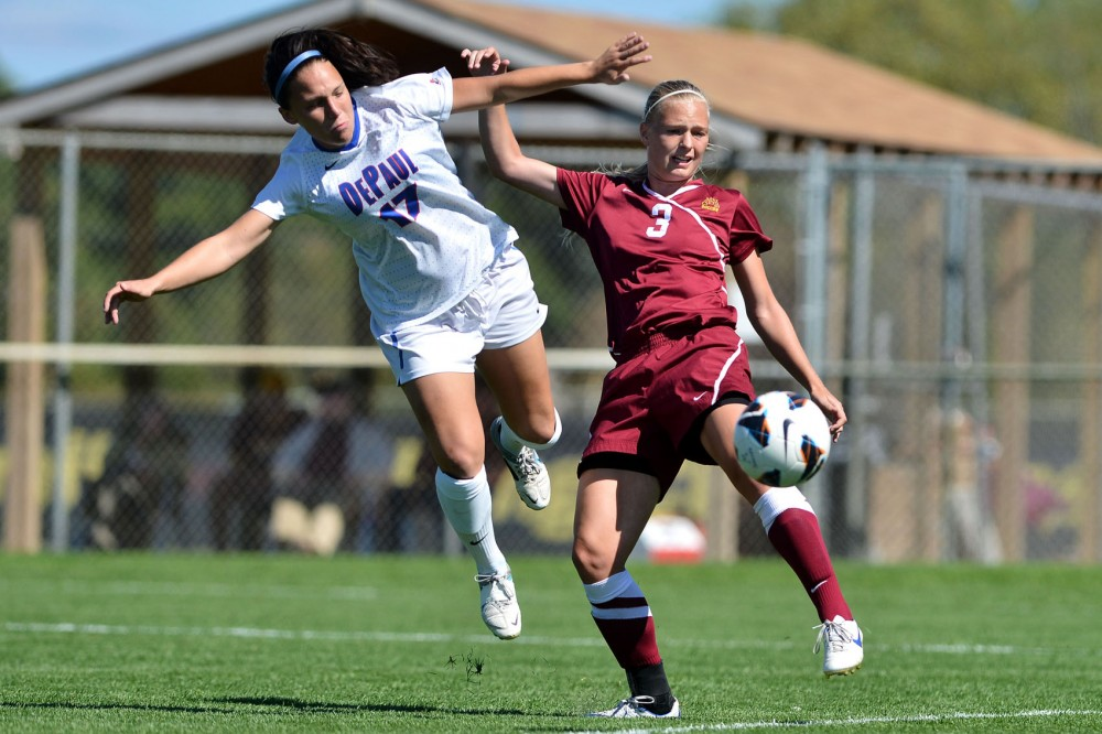 Minnesota forward Taylor Uhl receives a lob over the head of DePaul midfielder Rebekah Roller at Elizabeth Lyle Robbie Stadium on Sept. 9.