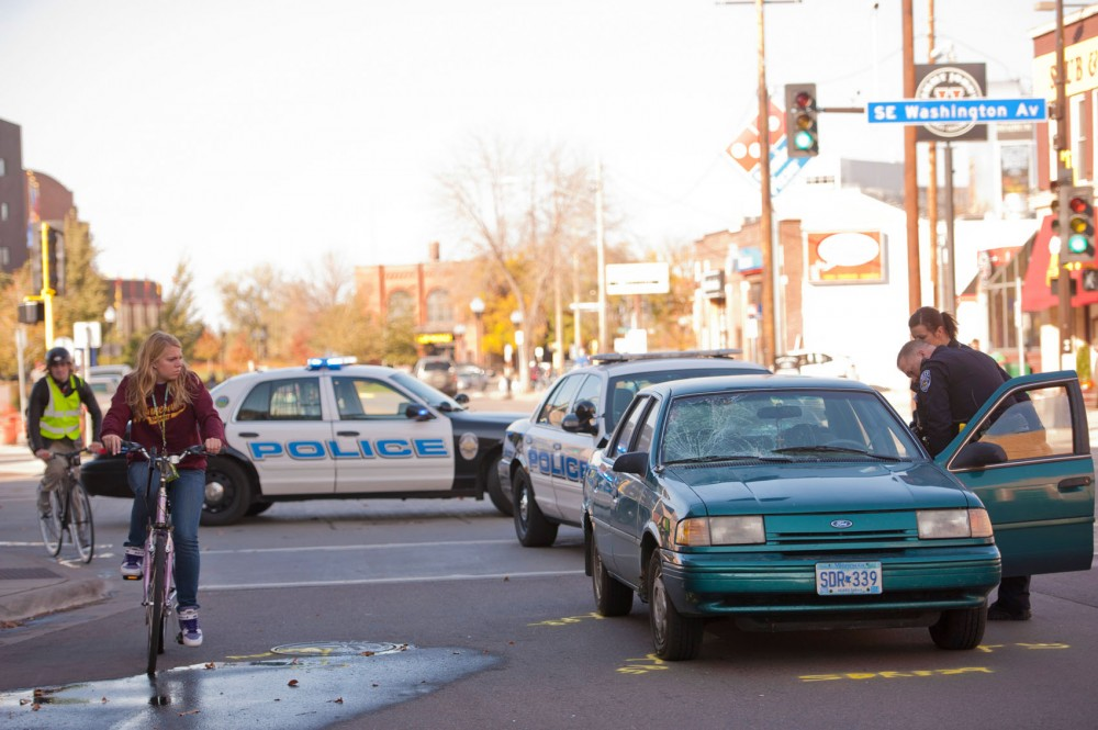 University of Minnesota police officers inspect the Ford Tempo that hit six pedestrians Sunday afternoon at the intersection of Washington Avenue and Oak Street Southeast. All six victims were taken to Hennepin County Medical Center with non-life-threatening injuries.