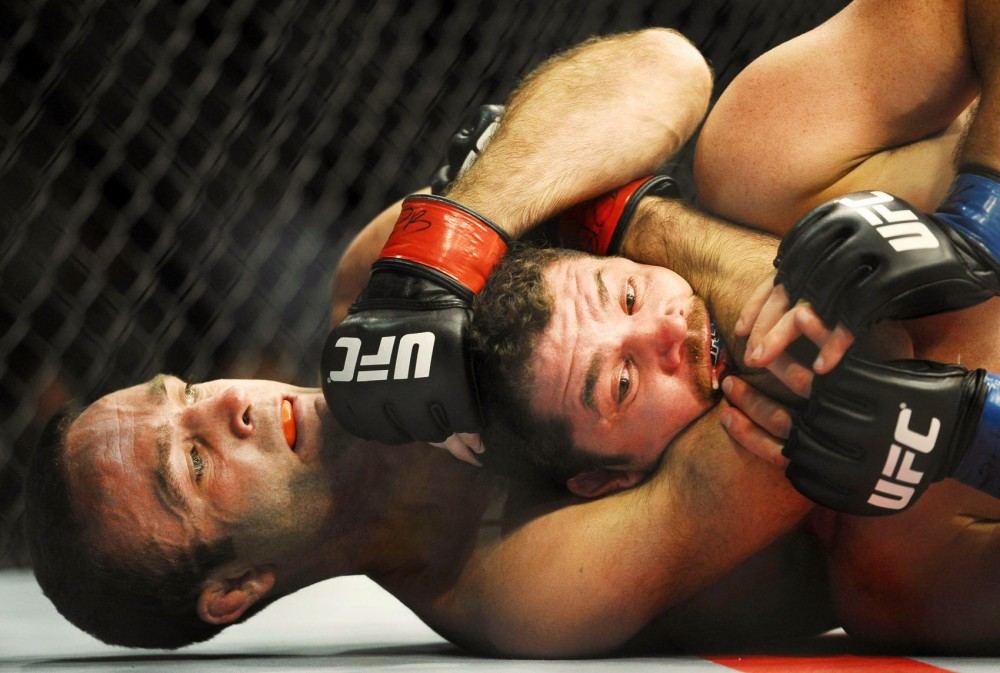 Former Minnesota wrestler Jacob Volkmann chokes his opponent, Shane Roller, during a UFC event Friday night at the Target Center. Volkmann won the bout in the first round after Roller failed to break his hold and tapped out.