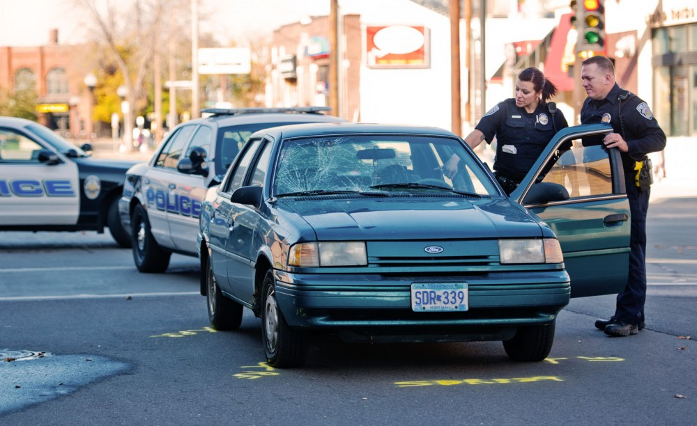 University of Minnesota Police officers inspect the Ford Tempo that hit four pedestrians Sunday afternoon at the intersection of Oak Street and Washington Avenue. All four victims were taken to Hennepin County Medical Center with non-life threatening injuries.