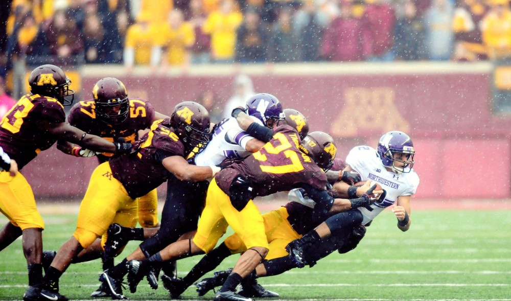A group of Minnesota defensive players sacks Northwestern quarterback Kain Colter on Saturday at TCF Bank Stadium. The Gophers lost to the Wildcats 21-13.