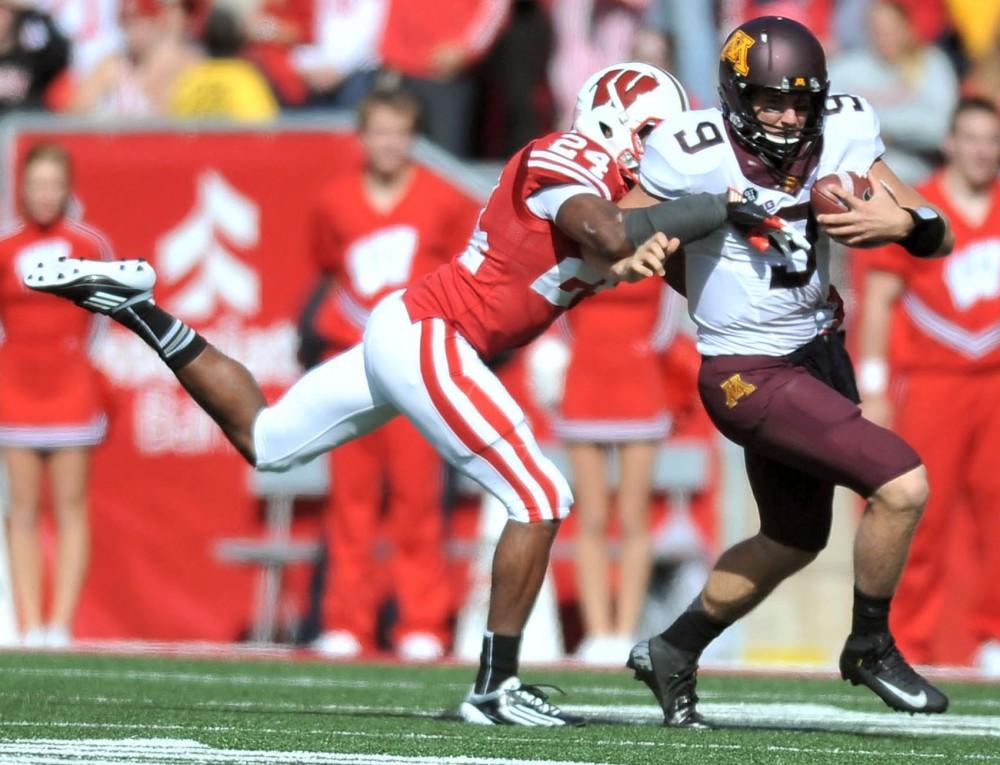 Wisconsin defensive back Shelton Johnson tackles Minnesota quarterback Philip Nelson on Oct. 20 at Camp Randall Stadium in Madison, Wisc.