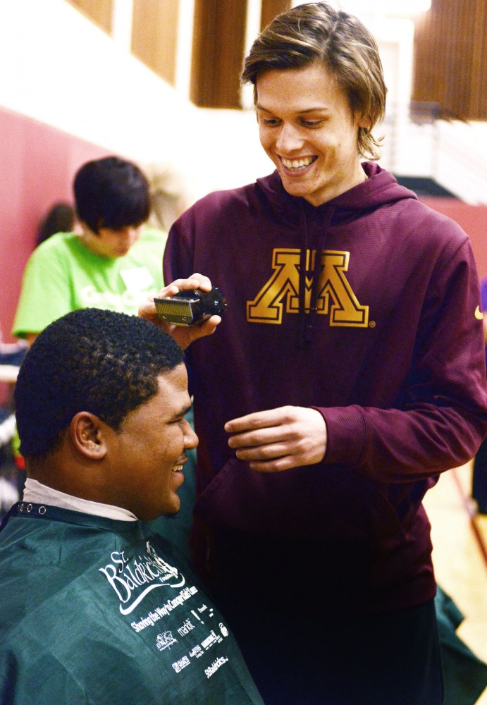 Connor Cosgrove, right, helps shave the head of teammate Roland Johnson during the St. Baldrick's Gophers Clip Cancer event Monday. Cosgrove, who was diagnosed with leukemia in 2010, spearheaded the partnership between St. Baldrick's Foundation and the University of Minnesota.