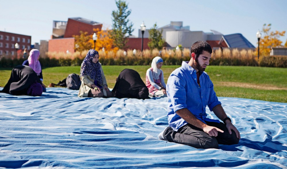 Amer Sassila, a member of the Muslim Student Association, engages in a noon prayer Tuesday on the front lawn of Coffman Union. The public prayer session was part of Multi-Faith Week, organized by the Interfaith Campus Coalition.