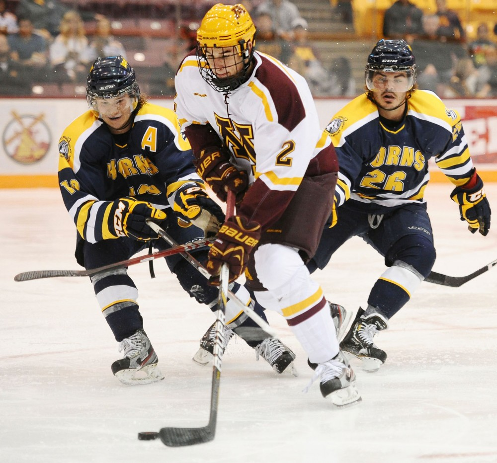 Minnesota defender fights for the puck during Saturday's game against Lethbridge at Mariucci Arena.