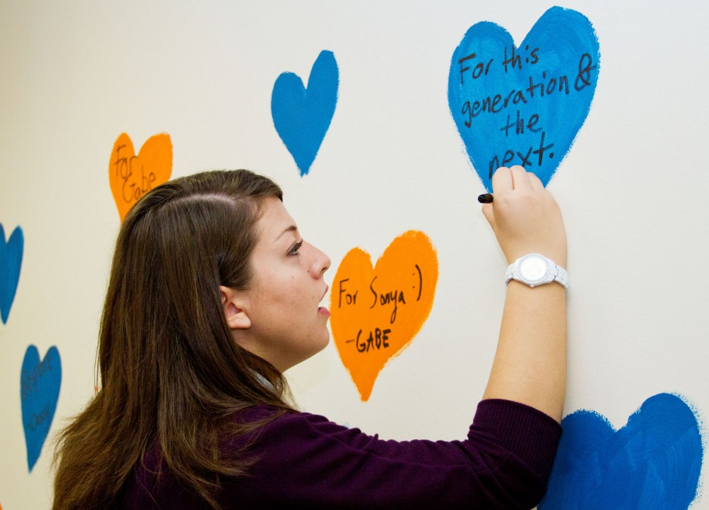 Alissa Clark helps decorate the walls in the new Minnesotans United for All Families office in Dinkytown. The organization held an open house on Saturday to kick off the final few weeks of the campaign.