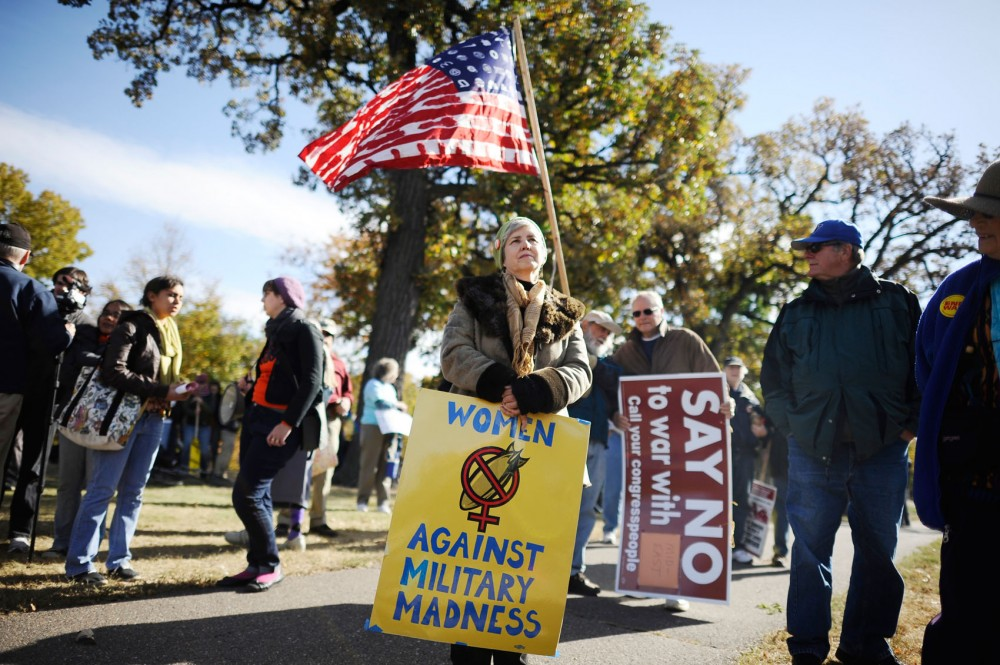 Women Against Military Madness protester Mary Beaudoin, center, demonstrates Sunday at Loring Park in Minneapolis.