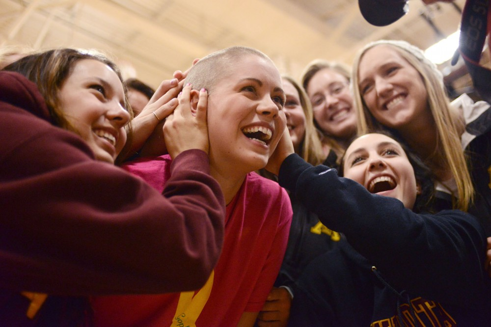 Gophers women's volleyball setter Mia Tabberson lets her teammates and friends feel her freshly-shaved head during the St. Baldrick's Foundation Gophers Clip Cancer event Monday. Tabberson and several other athletes shaved their heads to raise money for children's cancer research.