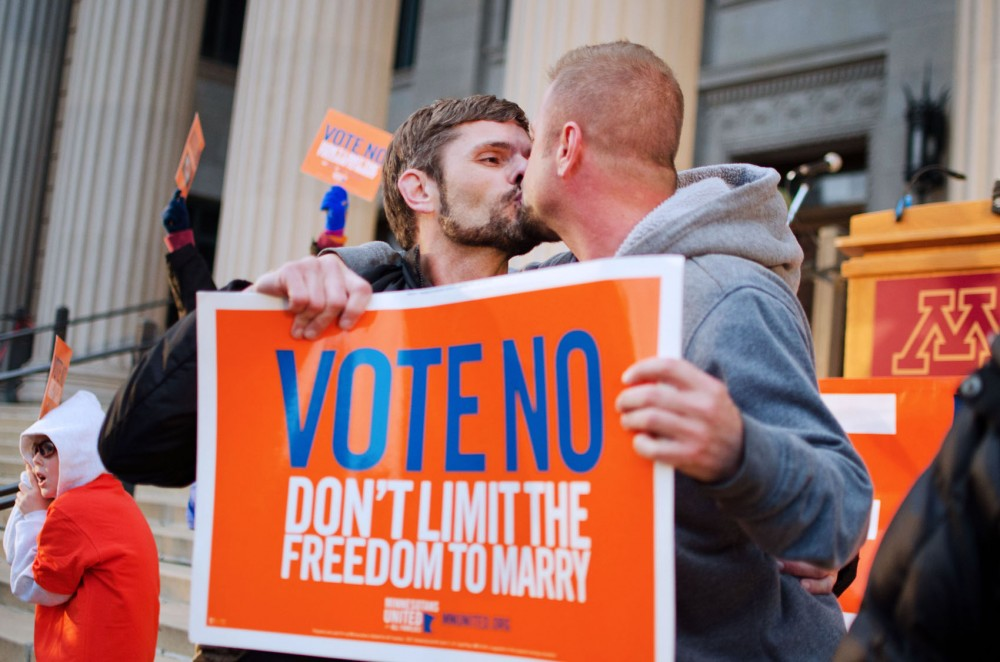 Bobby Long and Terry Tauger kiss on the steps of Northrop Plaza at the Vote No rally.