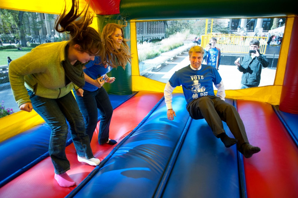 Conservation biology junior Jamee Snyder, College Democrats member Andrea Whitaker and Minneapolis Mayor R.T. Rybak play in a moon bounce Wednesday morning during Voterpalooza on Northrop Plaza.