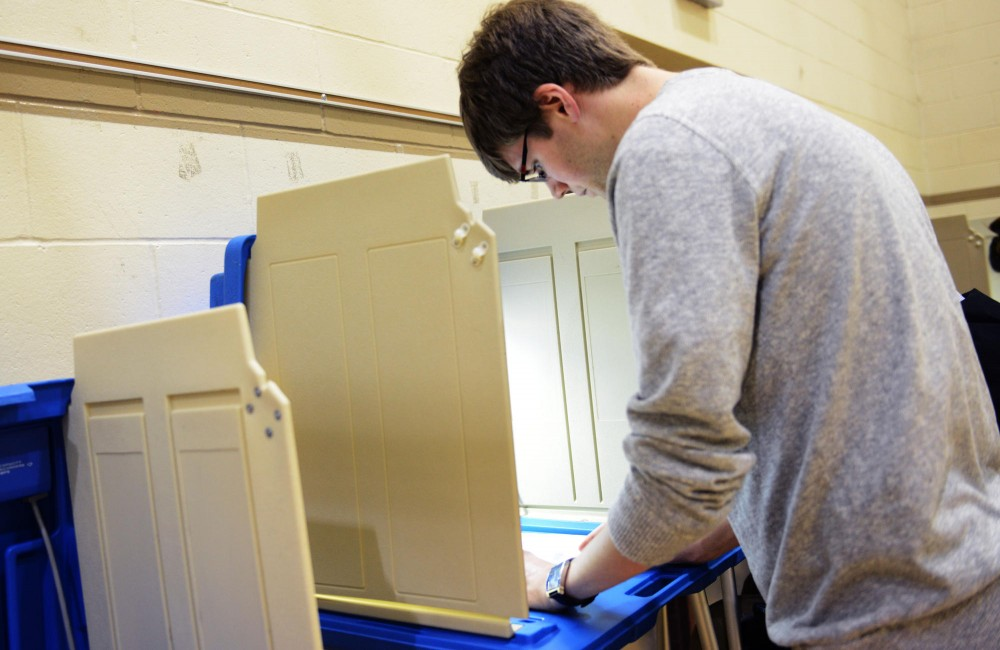 Masters of education student Reid Anderson fills out his ballot at the Marcy Open School polling station.