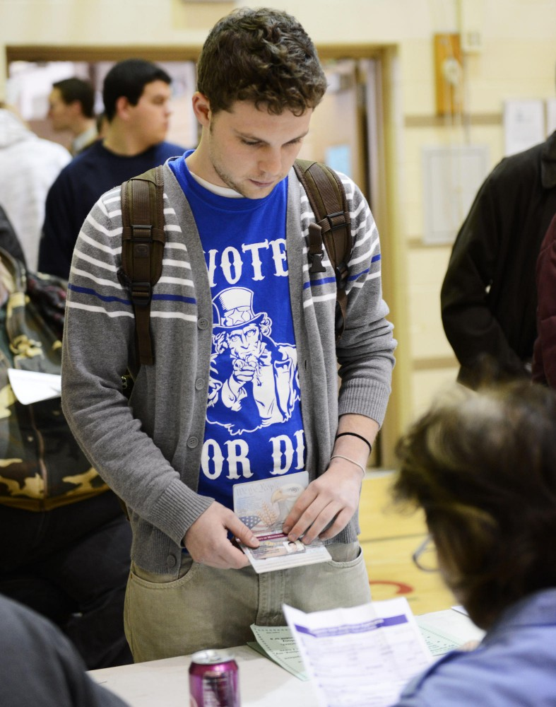 University student Kyle Thomas registers to vote at the Marcy Open School polling station.