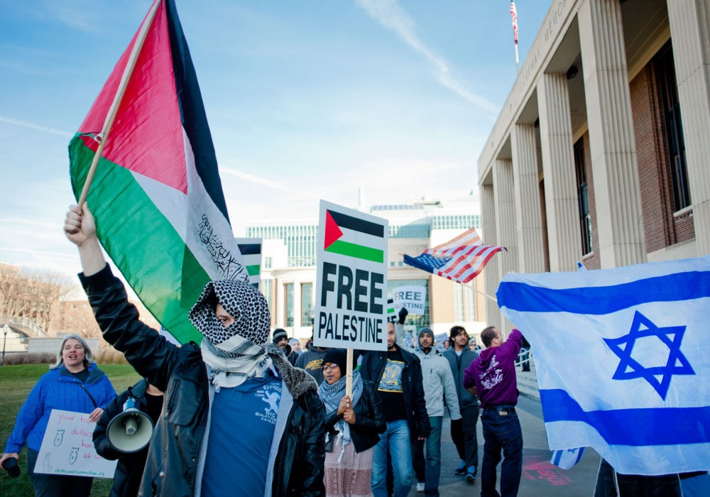 Physiology freshman Ashraf Abuhadid and other pro-palestinian protesters march past a contingent of pro-Israel demonstrators Friday in from of Coffman Union.