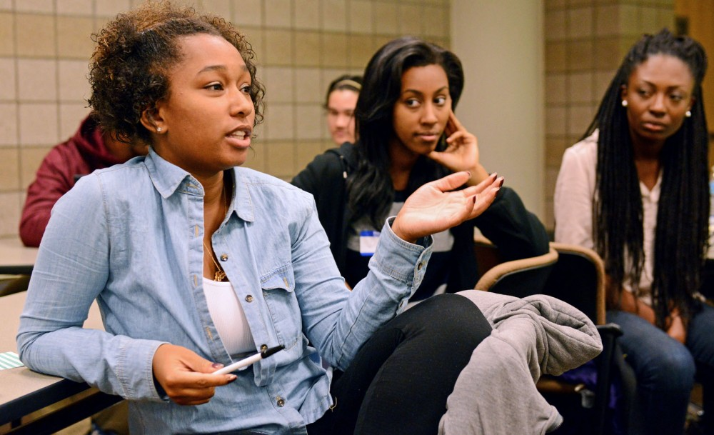 Food and agriculture junior Essence Bonner weighs in during Alpha Kappa Alpha's Race and Media event Thursday in the Molecular and Cellular Biology building. The event included large- and small-group discussions, as well as a Q&A with professors from both the University of Minnesota and St. Mary's University.