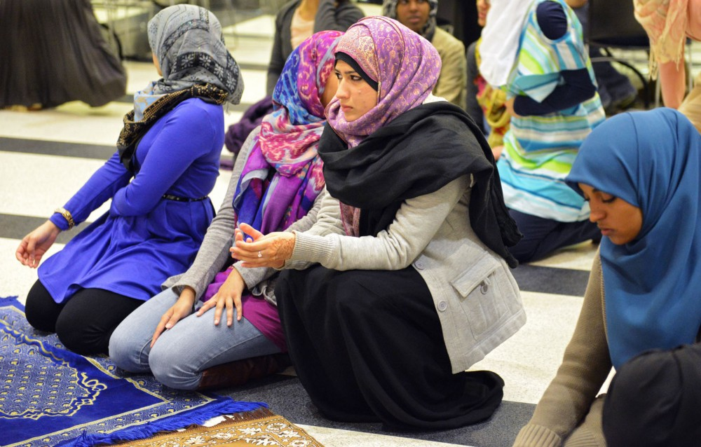 Psychology senior Omara Anjum kneels during the group prayer during the Muslim Student Association's Fast-a-Thon on Tuesday at Coffman Memorial Union.