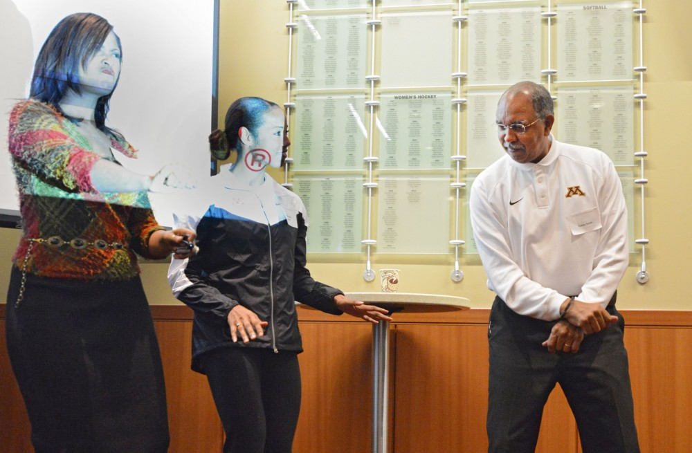 Robyne Robinson, left, former Olympian Shani Marks-Johnson, center, and Mens Basketball head coach Tubby Smith, right, dance to