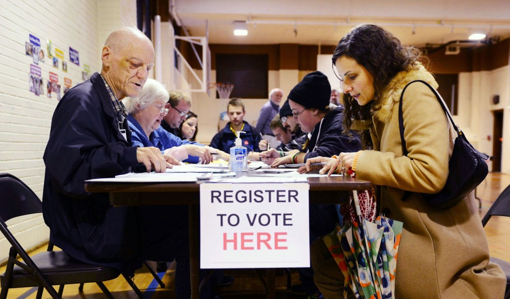 Minneapolis resident Maria Francisca Reines, right, registers to vote on Election Day at Pratt Community School.
