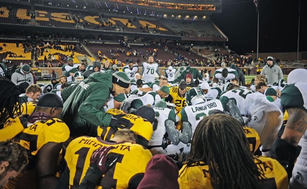 Michigan State head coach Mark Dantonio leads Minnesota and Michigan players in a prayer after the game, asking God to lay hands on Minnesota head coach Jerry Kill on Saturday, Nov. 24, 2012, at TCF Bank Stadium. Kill suffered a seizure during halftime of the Gophers' 26-10 loss.