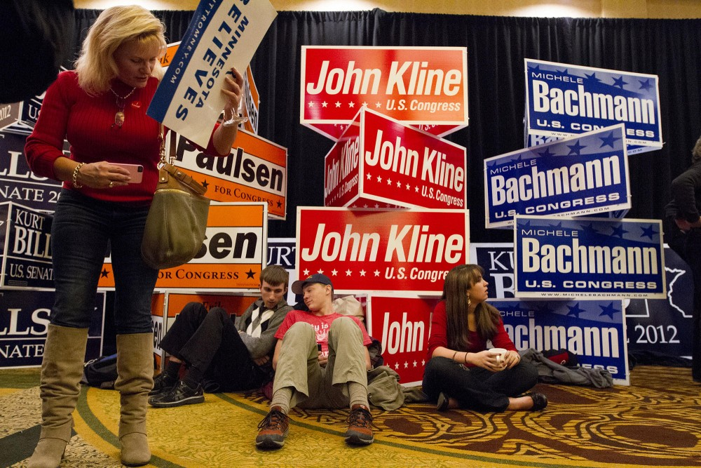 College students from the Patrick Henry College, located in Virginia, sit in front of GOP signs Tuesday at the GOP election night party in Bloomington, Minn. The three students are all leaders from the Generation Joshua Student Action Team sent to mobilize voters across the United States.