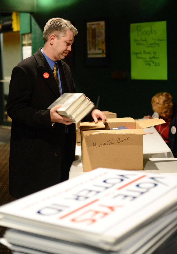 Dan McGrath, chairman of the organization Protect My Vote, puts away the campaign materials as the night comes to an end at OGaras Bar and Grill in St. Paul, Minn.