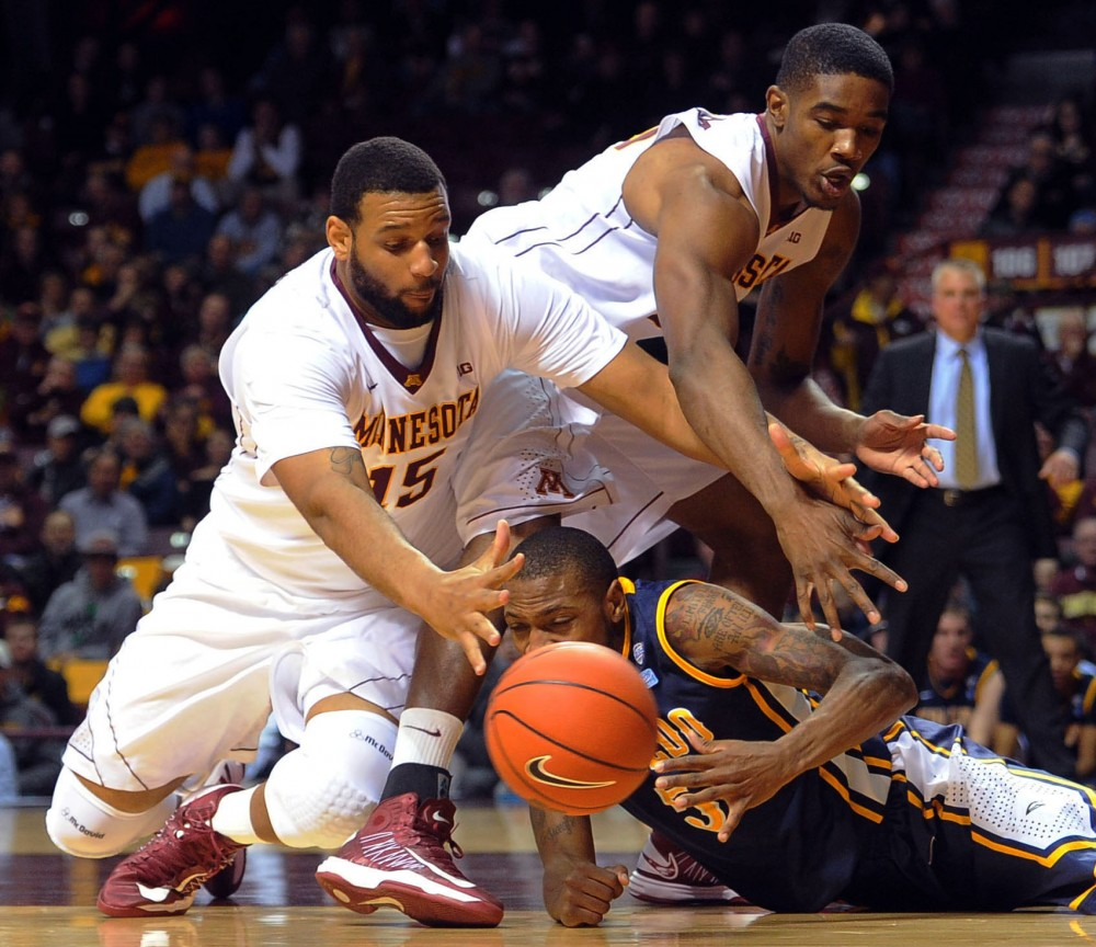 From left, Minnesota forward Maurice Walker, Minnesota forward Andre Ingram, back, and Toledo Rian Pearson fight for the ball after a rebound during a game Monday at Williams Arena.