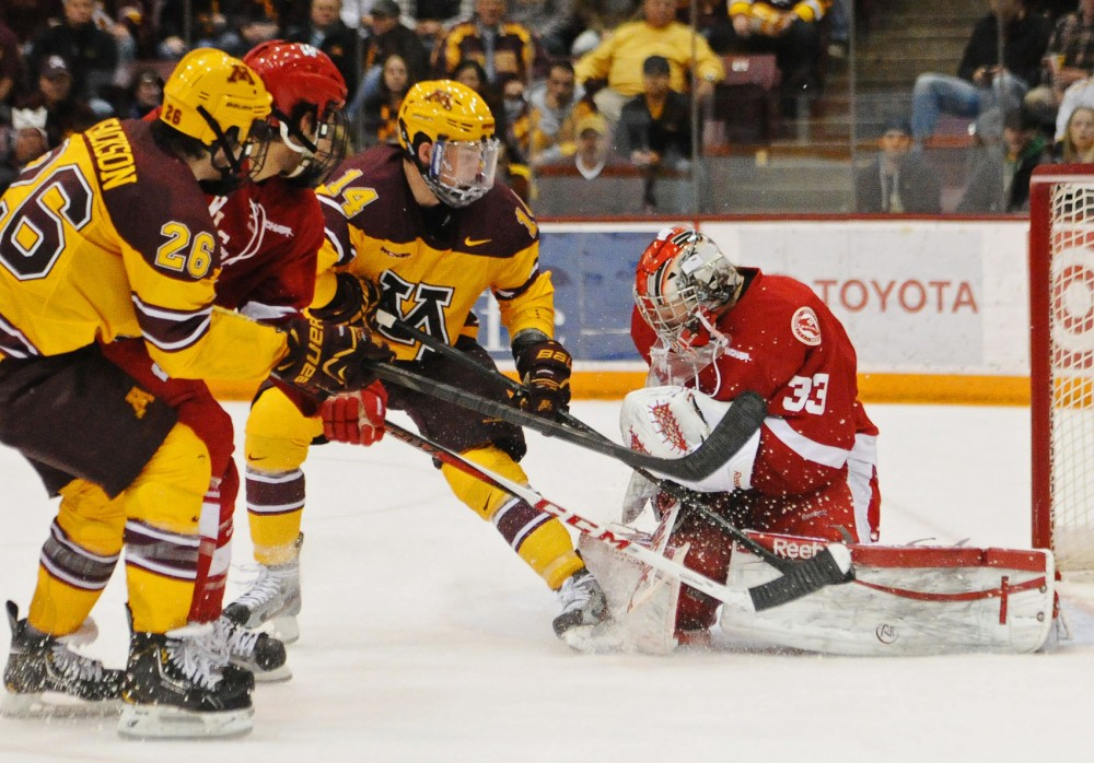 Minnesota forwards Christian Isackson, left, and Tom Serratore, center, make a play for a goal against Wisconsin goalie Joel Rumpel on Nov. 17, 2012 at Mariucci Arena.