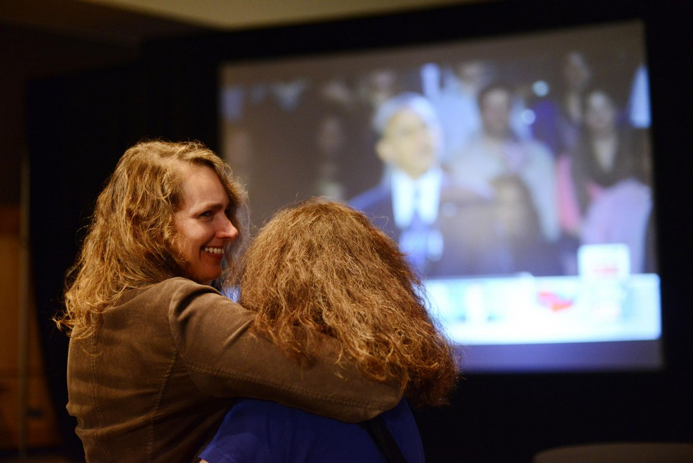 Debra Fitzpatrick and Lisa Miller embrace as they listen to President Obama talk as the election night nears to an end at the Minnesotans United election event in St. Paul, Minn.