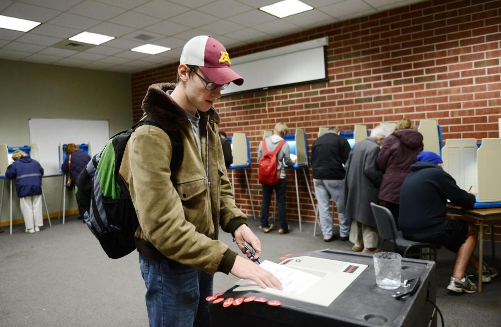 Freshman Matt Gallik turns in his ballot at the Falcon Heights City Hall.
