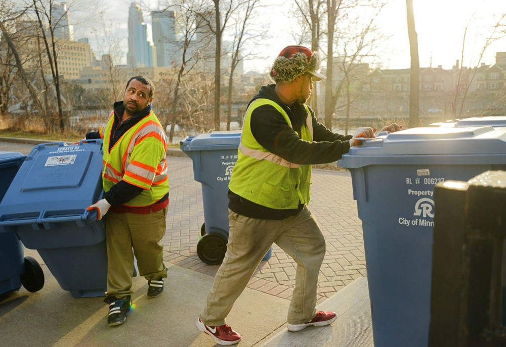 City of Minneapolis employees Keith Barker, left, and Darius Locke, right, remove leftover one-sort recycling carts on Wednesday, Nov. 21, 2012, on Nicollet Island in Minneapolis. Some residents in neighborhoods surrounding the University should see their new carts as soon as this week.