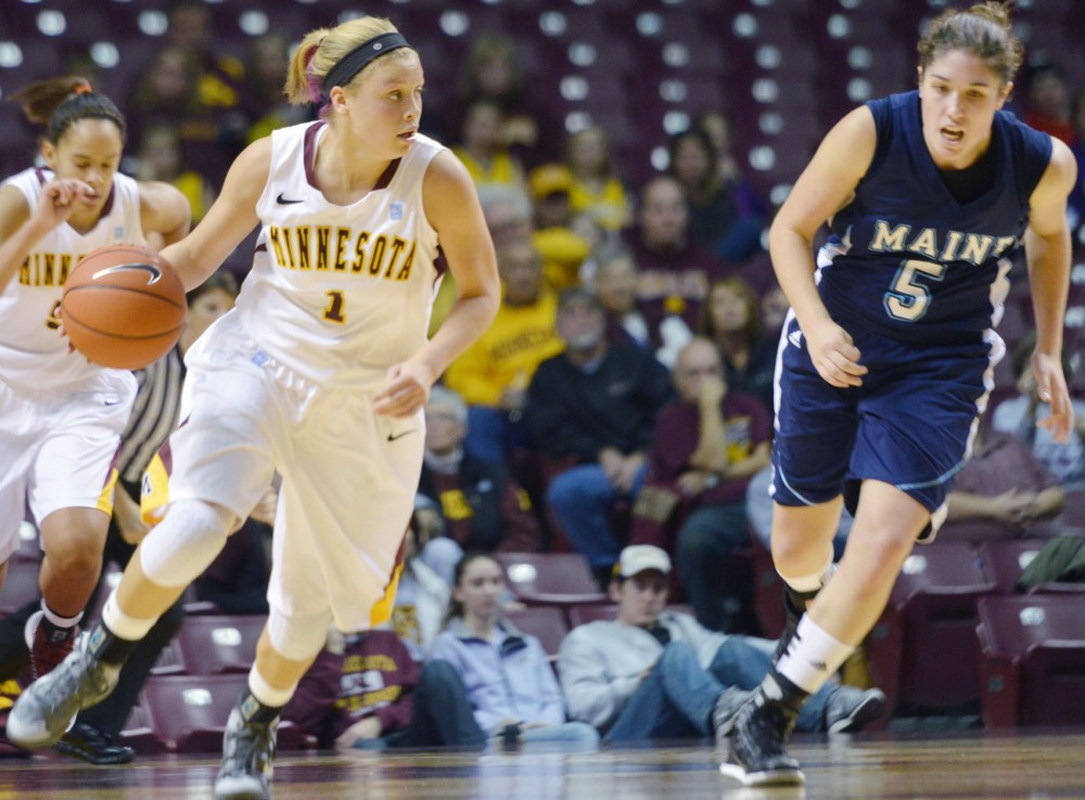 Minnesota guard Rachel Banham rushes the ball past Maines Danielle Walczak on Sunday at Williams Arena. The Gophers defeated the Maine Black Bears 77-60.