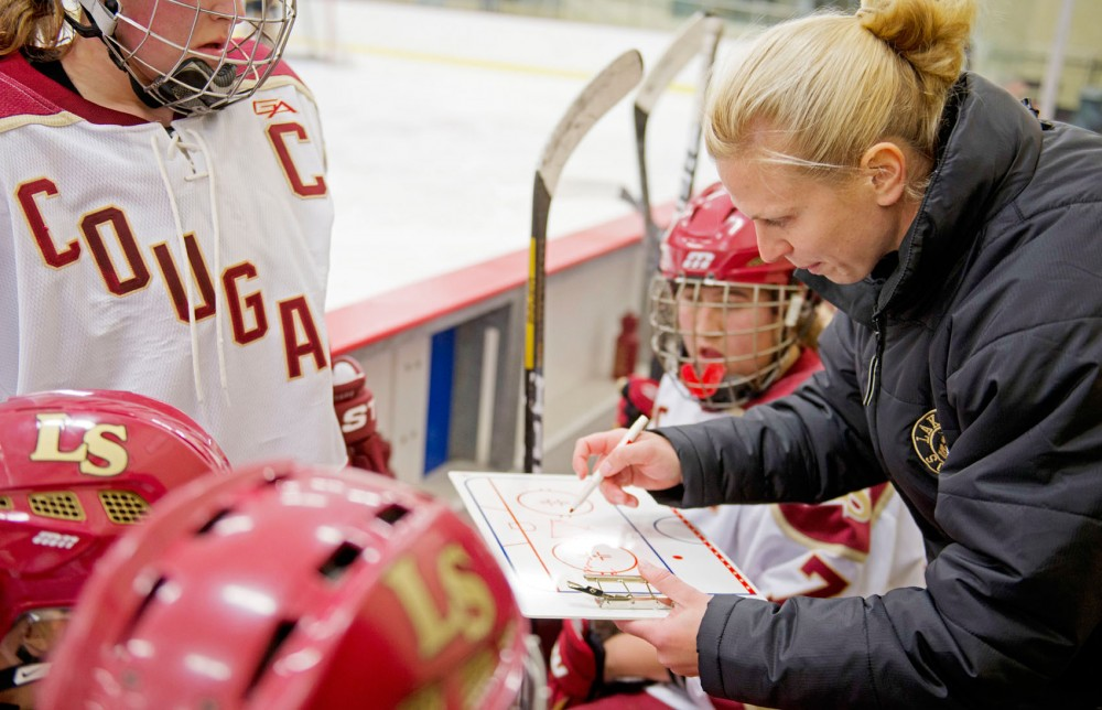 Natalie Darwitz discusses strategy with  the Lakeville South High School girls hockey team during a game against Burnsville High School on Nov. 6 at Hasse Arena in Lakeville, Minn.