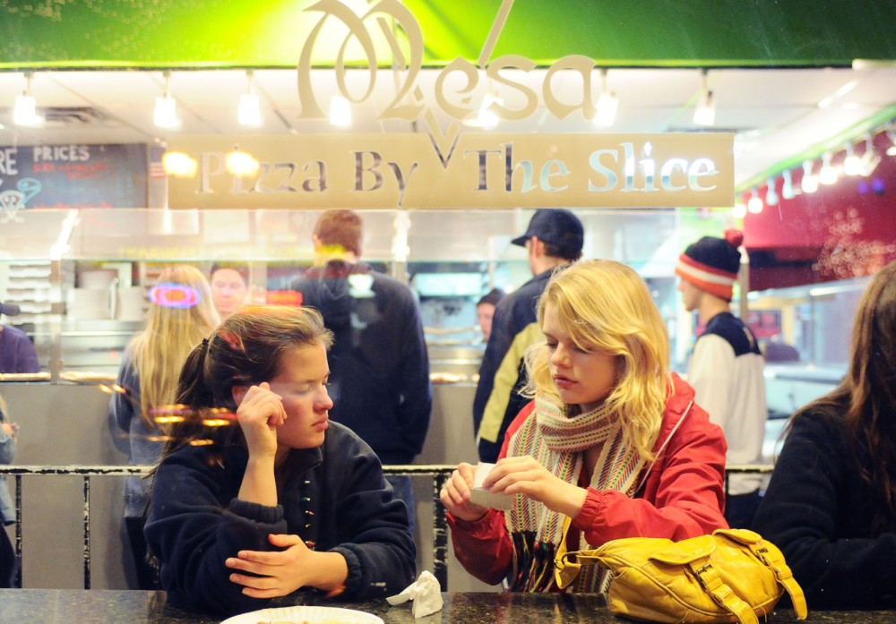 Freshman Madelyn Kraft, right, and friend Eva McCauley enjoy some late-night pizza Saturday at Mesa Pizza.