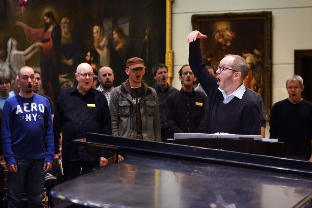 Artistic director Ben Riggs leads the members of the Twin Cities Gay Men's Chorus in vocal exercises. Riggs started as the artistic director in August.