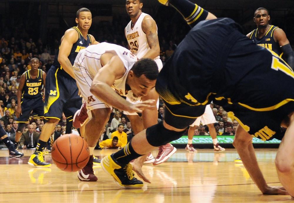 Michigan player falls over Minnesota guard Joe Coleman, Thursday night at Williams Arena.