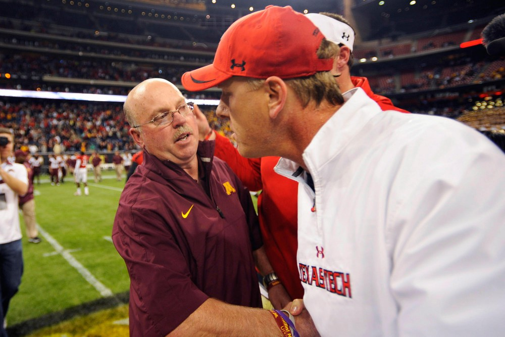 Minnesota head coach Jerry Kill congratulates Texas Tech interim head coach Chris Thomsen on their win.