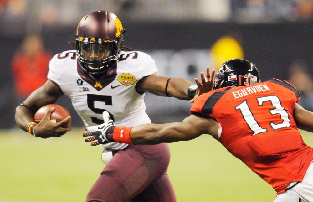 Minnesota quarterback MarQueis Grayson rushes the ball.