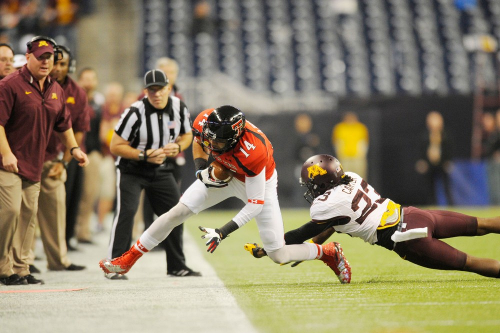 Minnesota defensive back Michael Carter tackles Texas Tech wide receiver Darrin Moore.