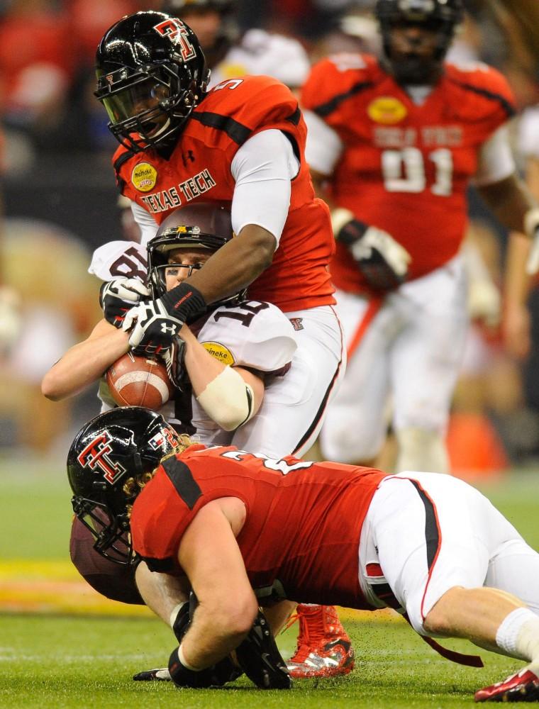 Texas Tech's Tre' Porter and Blake Dees tackle Minnesota wide receiver Derrick Engel.