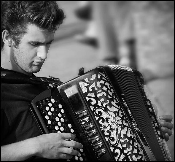 Patrick Harison jamming on his 40 pound accordion — essentially a bellows powered harmonica.