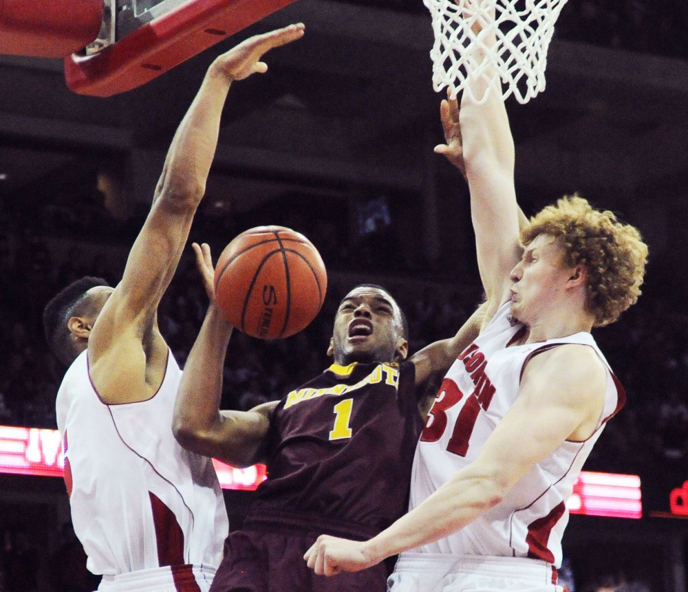 Minnesota guard Andre Hollins (1) competes for the ball against Wisconsin forward Mike Bruesewitz on Saturday at the Kohl Center in Madison, Wis. The game ended in a 44-45 loss for the Gophers.
