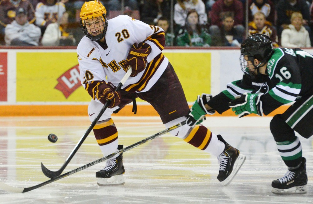 Minnesota defenseman Mark Alt passes past North Dakota forward Mark MacMillan on Jan. 19, 2013 at Mariucci Arena. On Friday the Gophers defeated the Sioux 5-1, but Saturday's game ended in a 4-4 tie.