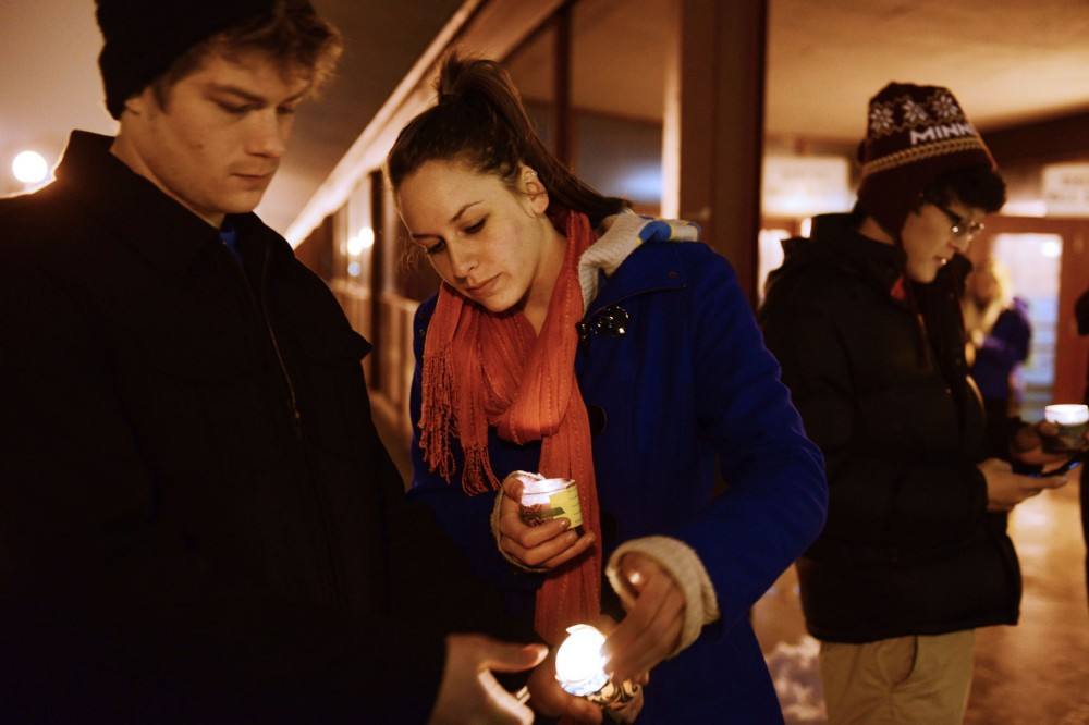 Strategic communication junior Karen Elizondo lights microbiology junior Dane Elmquist's candle during a vigil for University student Matt Challou on the Washington Avenue Bridge on Monday, Jan. 28, 2013. Challou committed suicide Jan. 21, 2013.