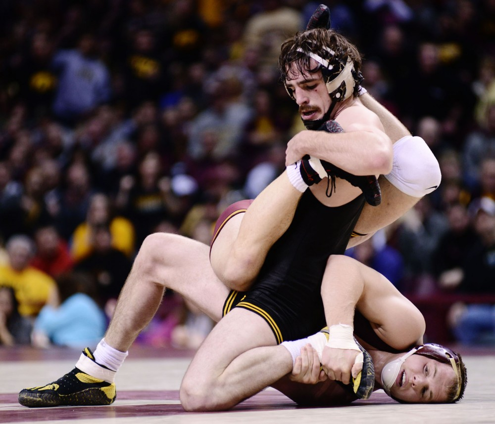 Minnesotas Logan Storley attempts to take down Iowas Mike Evans on Saturday, Jan. 26, 2013, at Williams Arena.