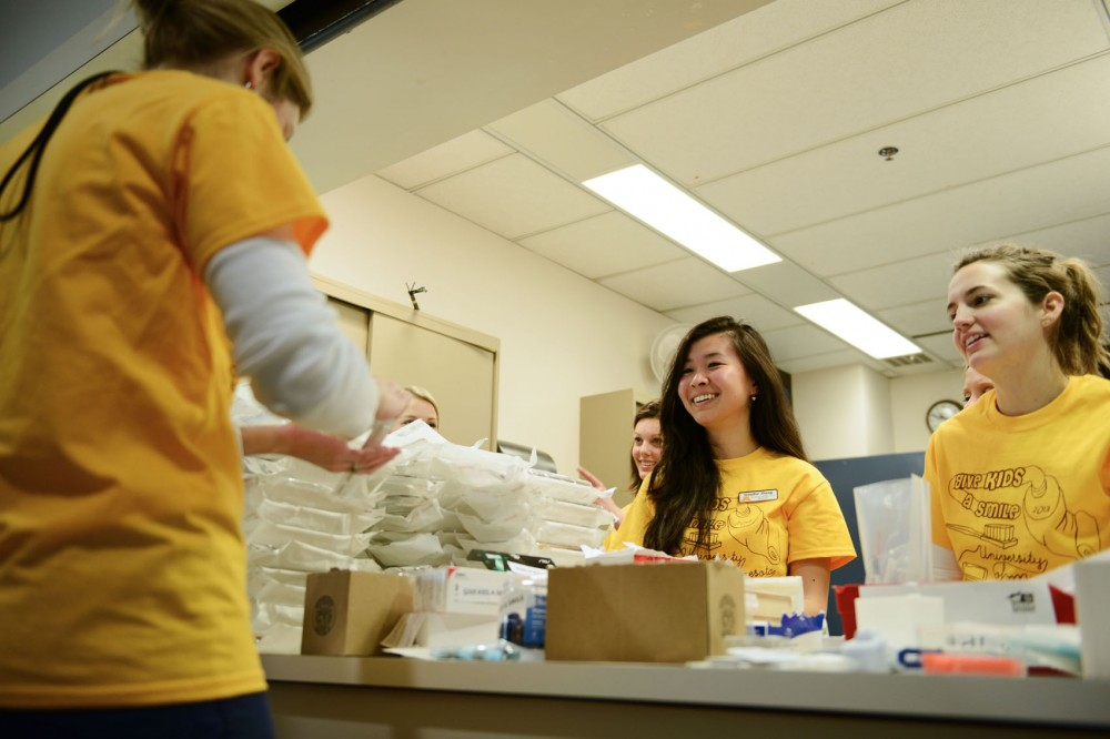 Dental students Amber Kroke, right, and Jennifer Zhang provide the cleaning materials to other students during the Give Kids a Smile Day on Saturday, Feb. 2, 2013, at Moos Tower.