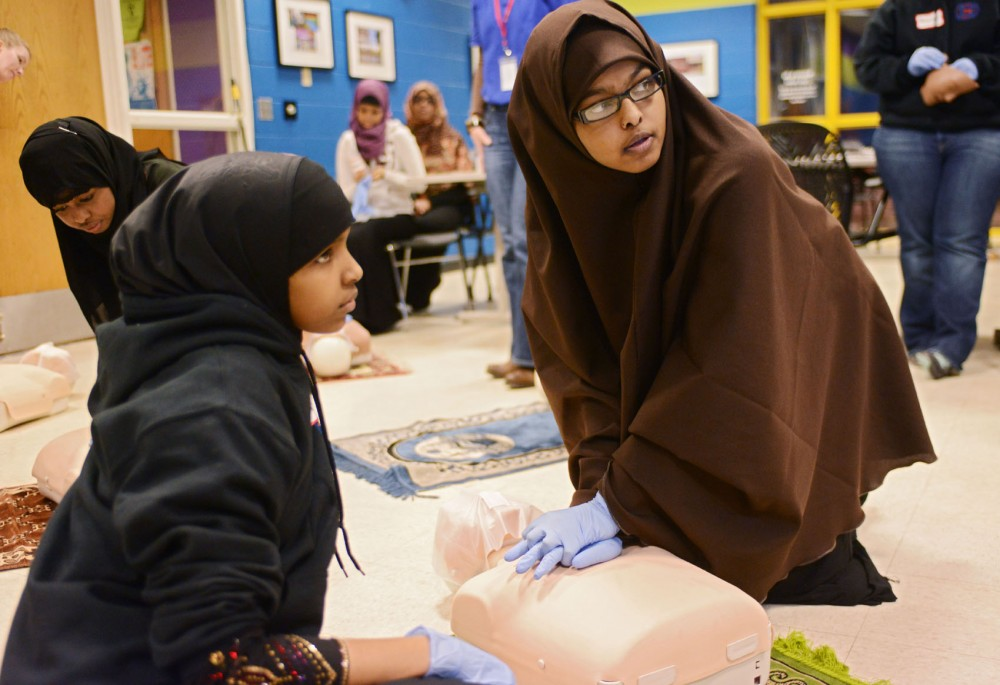Sixteen-year-old Ubah Salad, right, and 20-year-old Mona Abdullahi practice chest compressions on a test dummy Tuesday, Feb. 19, 2013, at the Brian Coyle Center in Minneapolis. The Minneapolis Fire Department started the program to educate youth and improve relations between the department and the Cedar-Riverside community.