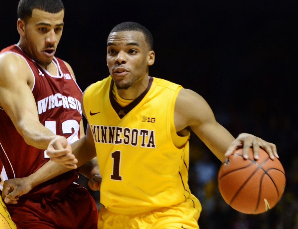 Minnesota guard Andre Hollins dribbles past a Badger on Thursday, Feb. 14, 2013, at Williams Arena.