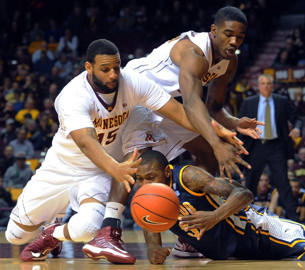 Minnesota forwards Mo Walker, left, and Andre Ingram and Toledo's Rian Pearson fight for the ball after a rebound Monday, Nov. 12, 2012, at Williams Arena.